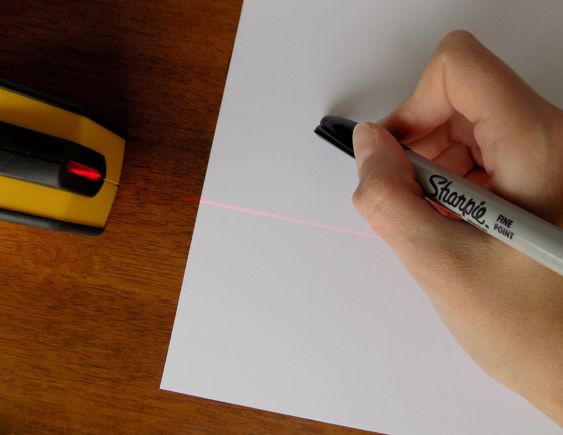 Step 3.1.  Begin lettering using a ruler or a laser leveler to keep your words even with the paper. Write your biggest word first, then fit the smaller phrases around it. In this design, I lettered their last name first, then added 'Mr. & Mrs.' to the top and the date on the bottom.