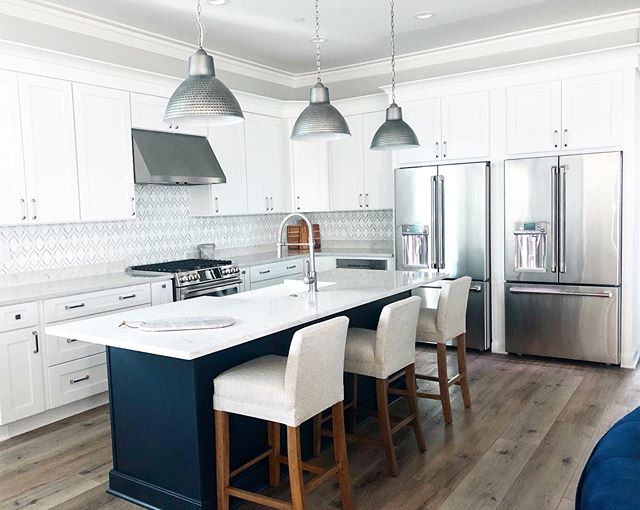 """It's been a loooong install week on this beautiful beach rental property. When designing this kitchen, I wanted it to scream """"vacation!!"""" and I think the 2 refrigerators really cement that sentiment ☀️. . . #kitchen #kitchendesign #navykitchen #navykitchens #navykitchenisland #kitchenisland #coastaldecor #coastaliving #30ainteriordesign #30ainteriordesigner #interiordesign #30a #beachhousedecor #miramarbeach #beachhousestyle #kitcheninspo #newbuild #cafeappliances #newbuildhouse #lvpflooring #whitecabinetry #forevermarkcabinetry #deltafaucet #beachyglaminteriors"""