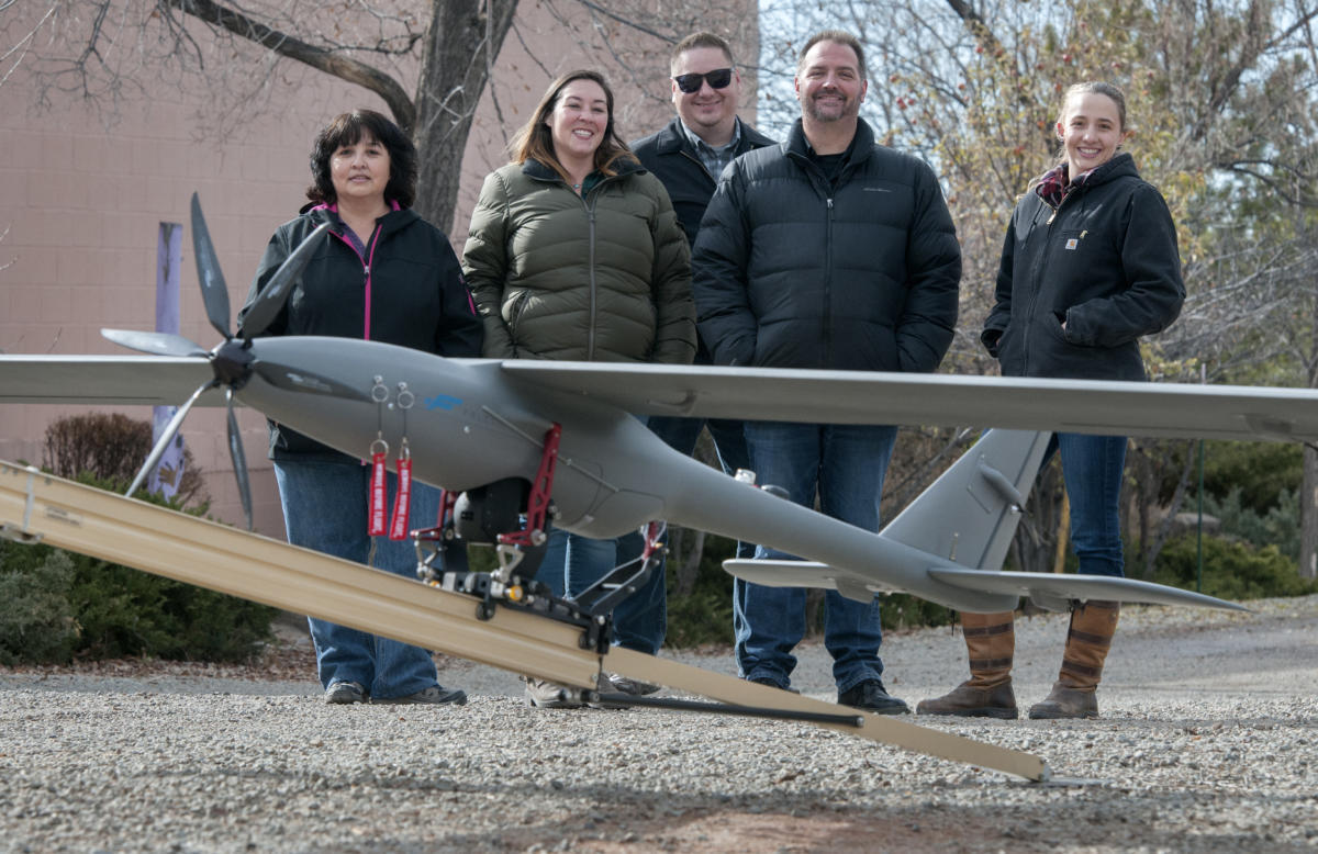 Wildflower International employees pose with their Silent Falcon drone at their office in Santa Fe. From left, Karen Sandoval, Laura Salazar, Michael Wahl, Rob Scism, all flight crew members, and Jenna deCastro the outside account executive for DOE. (Eddie Moore/Albuquerque Journal)