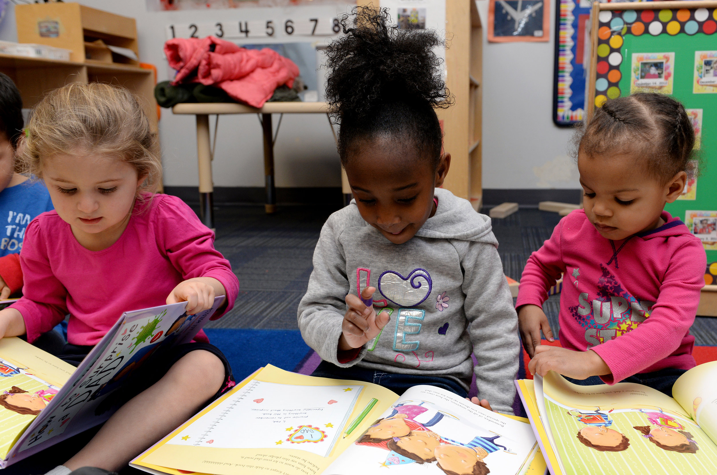 Three preschool students read books at the Child Development Center at Langley Air Force Base, Va., Feb. 16, 2016.  Photographer: Kaylee Dubois