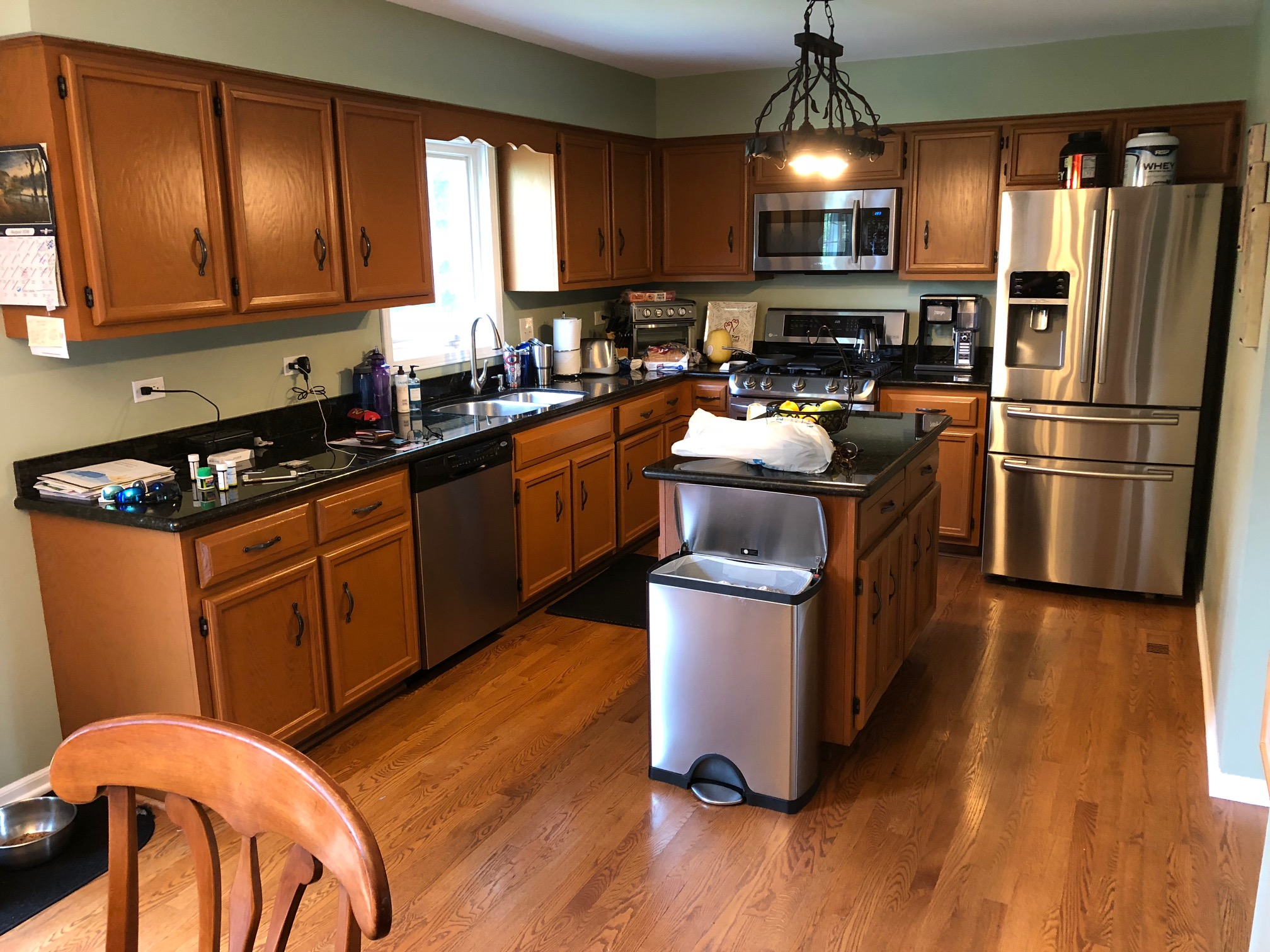 BEFORE - dark wood, cabinets, dark counters, outdated knobs and pulls, outdated light fixtures, painted backsplash