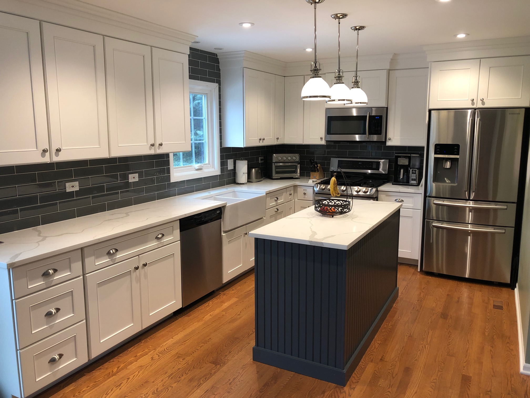 AFTER - BRIGHT!!! white cabinets, quartz counters, new drawer knobs/pulls, modern backsplash and light fixtures