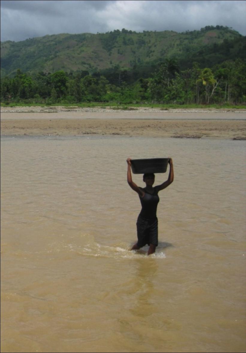 Woman wading through Grande Riviere du Nord near Cap Haitien, Haiti.