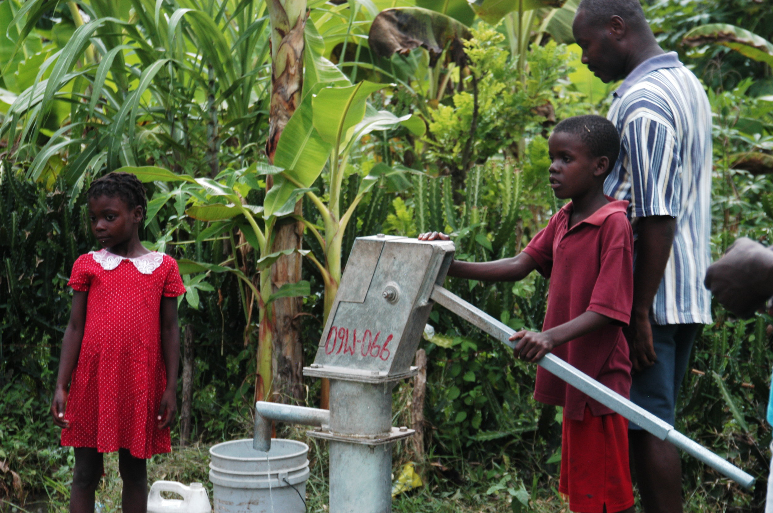 Father and son at a hand pump near Cap Haitien during the cholera epidemic.