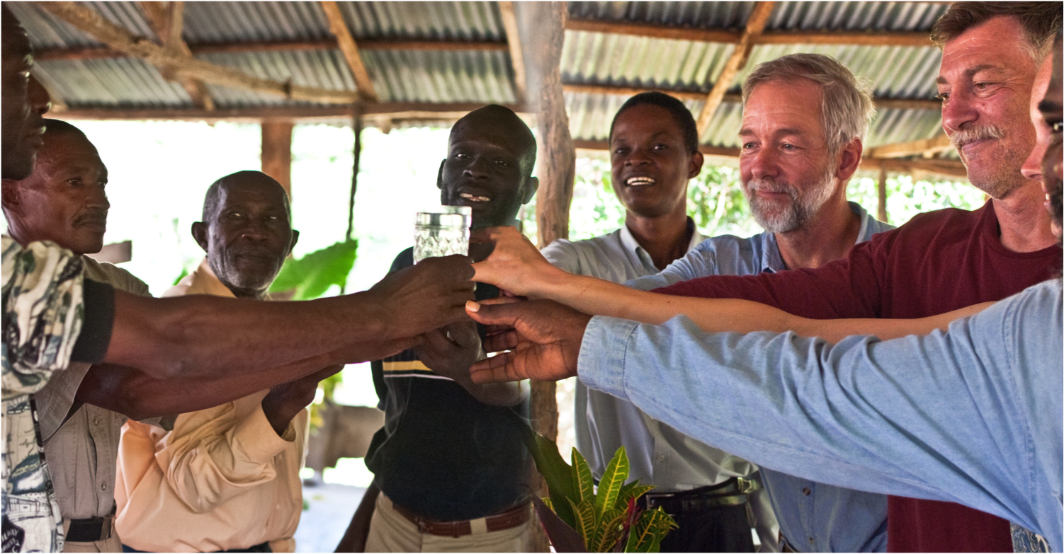 Volunteers and community leaders celebrate the first glass of clean water from the completed water system at La Soufriere, Haiti.
