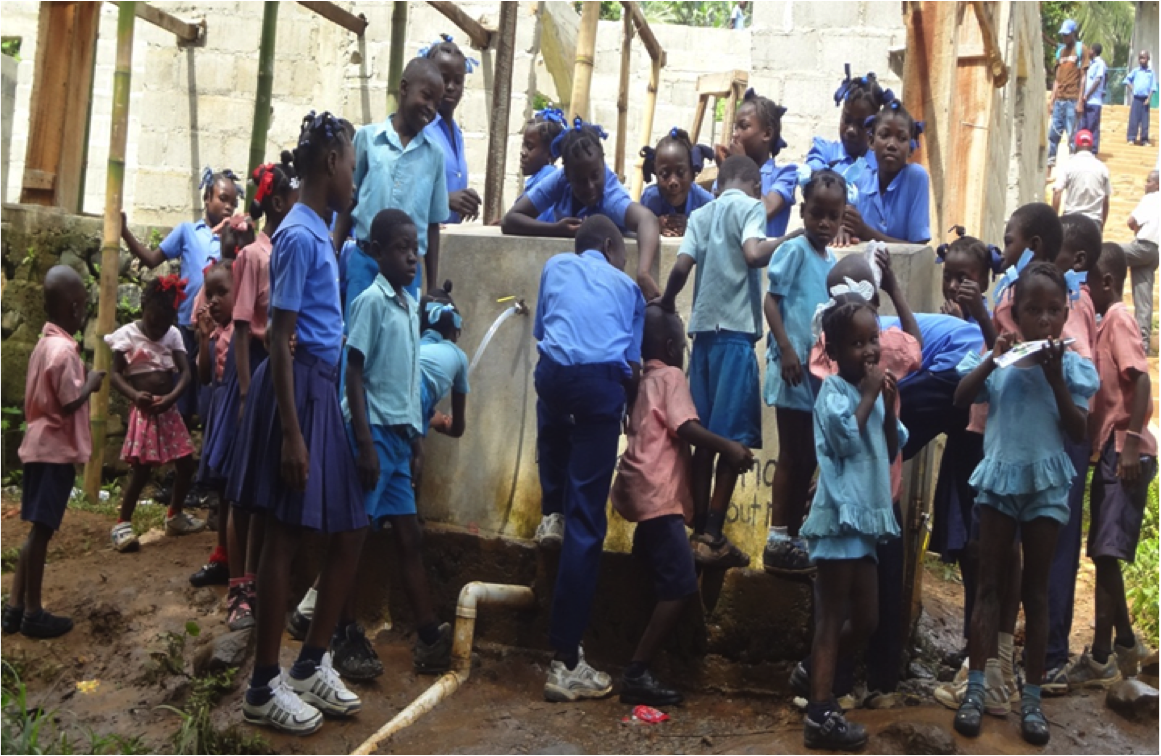 School children gather around the standpipe that provides clean water to the population at La Soufriere.