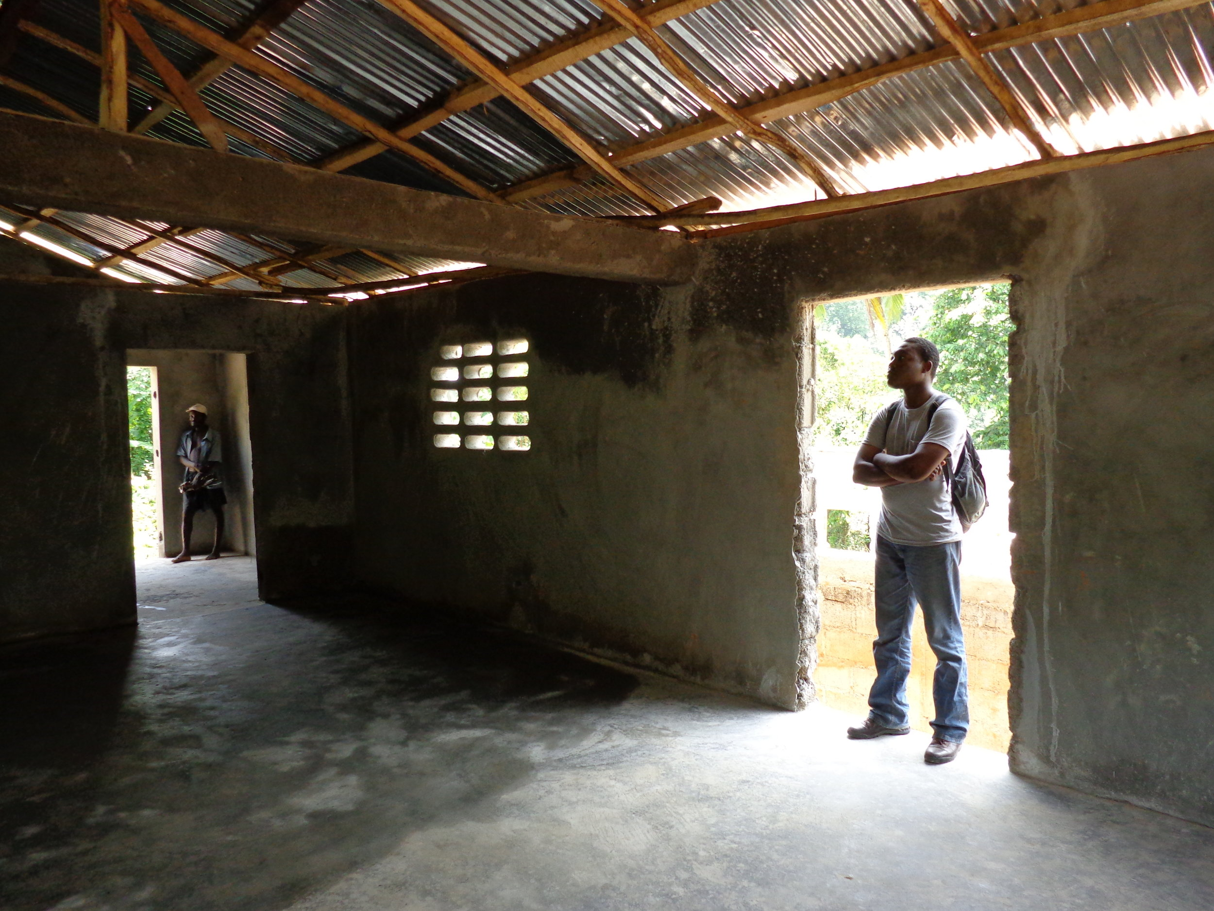 GROW Haiti board member, Snarly Colas, stands in the health center building.