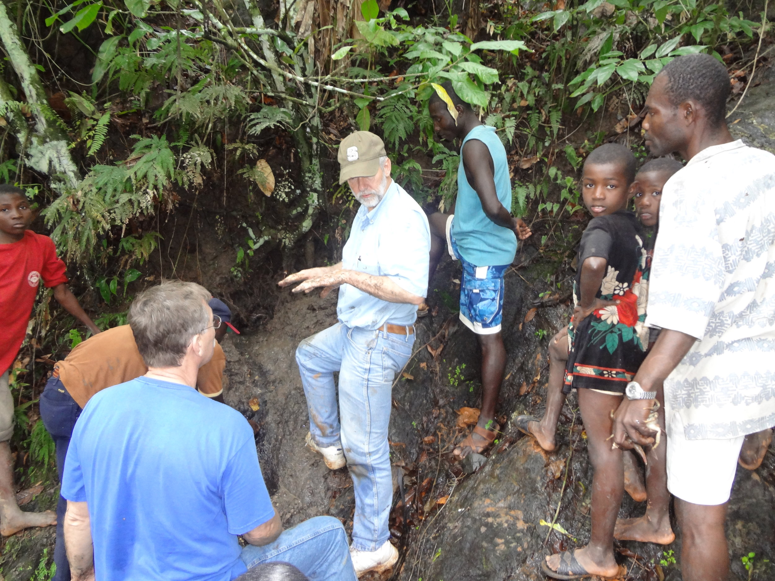 Volunteer engineers and local youth discuss the best ways to capture water from the spring above the health center.