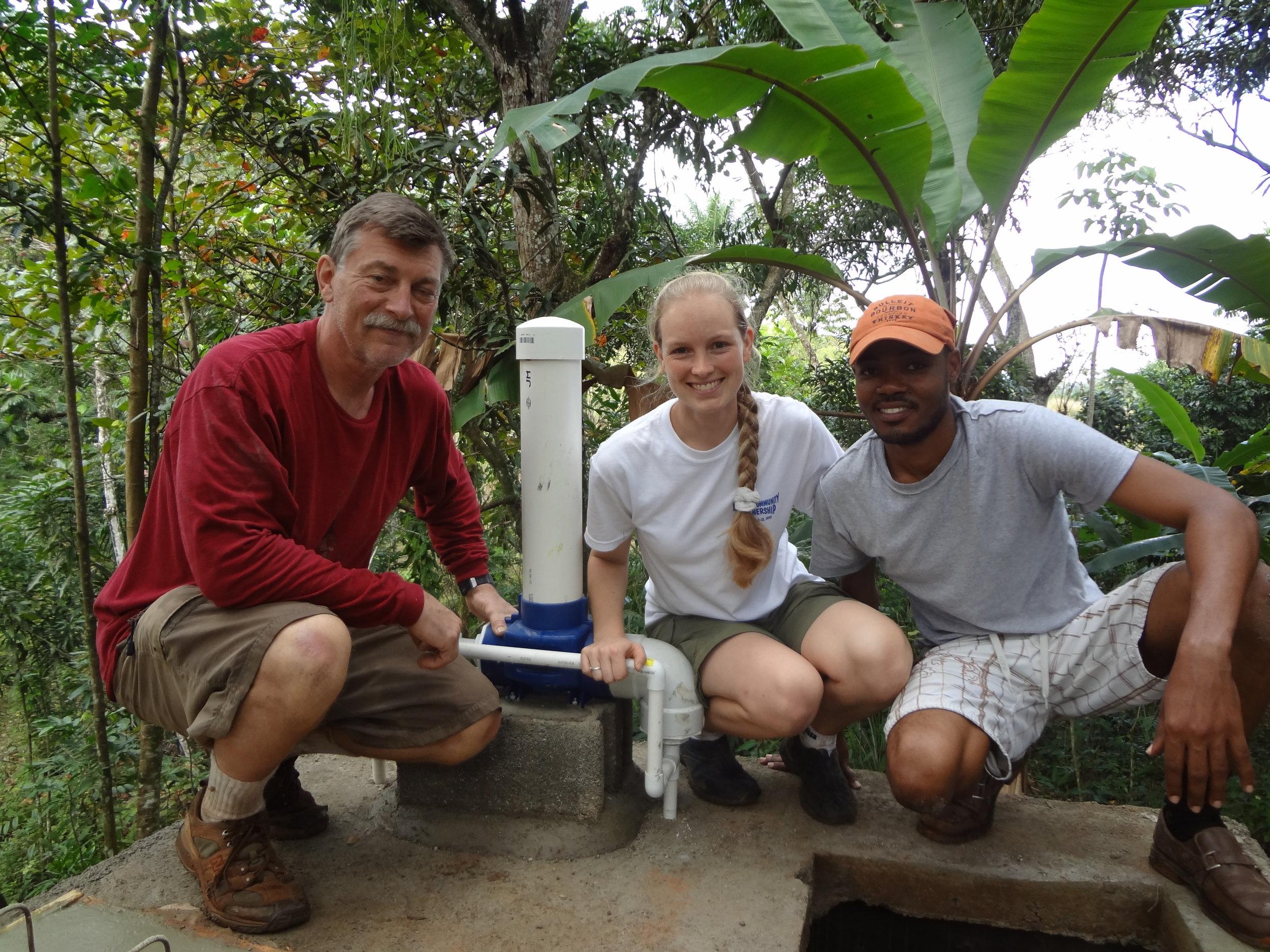 Volunteer engineer, Leo Mulcahy, GROW Haiti board member, Mac Henri, and Meike pose with the chlorinator on top of the completed water cistern.