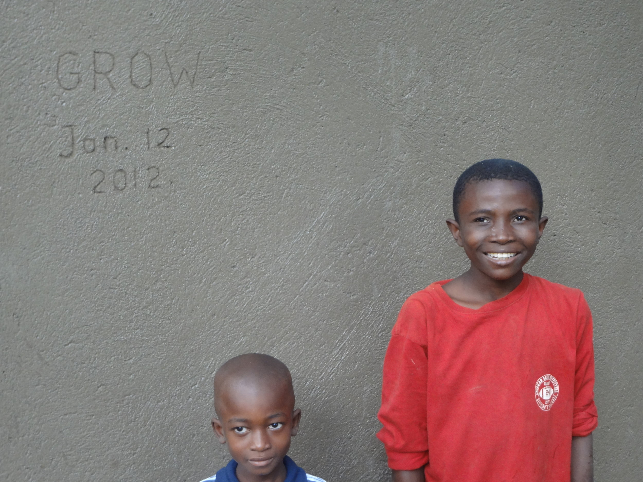 Local children who helped with the construction stand proudly next to the completed cistern.