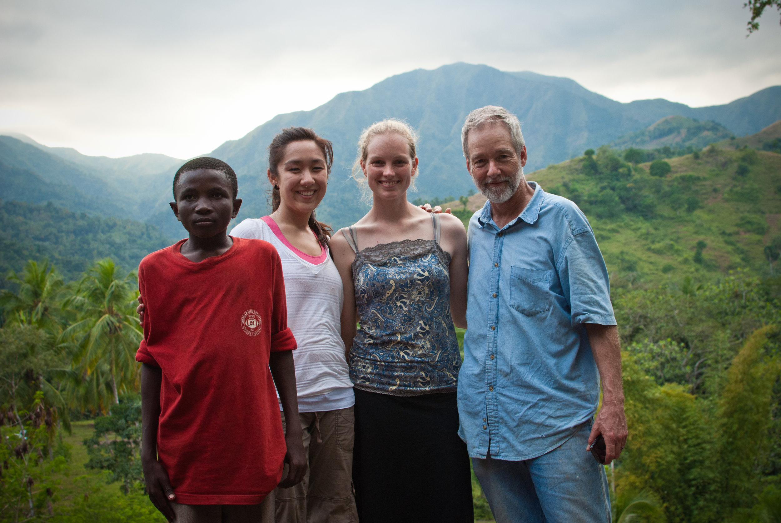 GROW volunteers and local youth pose in front of the stunning mountain backdrop near Soufriere.