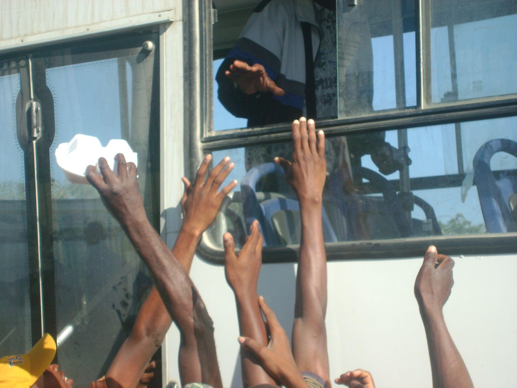 Hands reaching for food and water being distributed from a bus in Port au Prince, Haiti in the days following the earthquake.