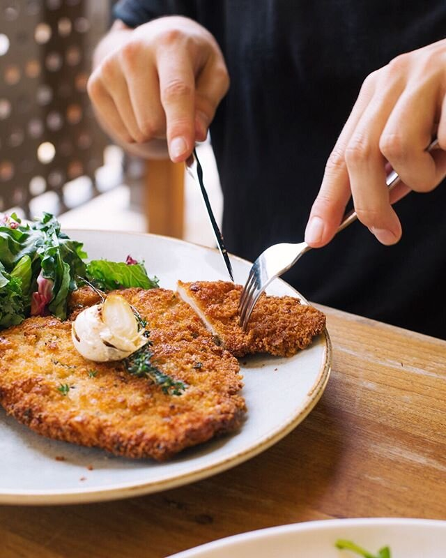 This golden-crumbed chicken schnitzel is a long-standing favorite on our lunch and dinner menu. Served with a leafy green salad—it's one of our favorite things.