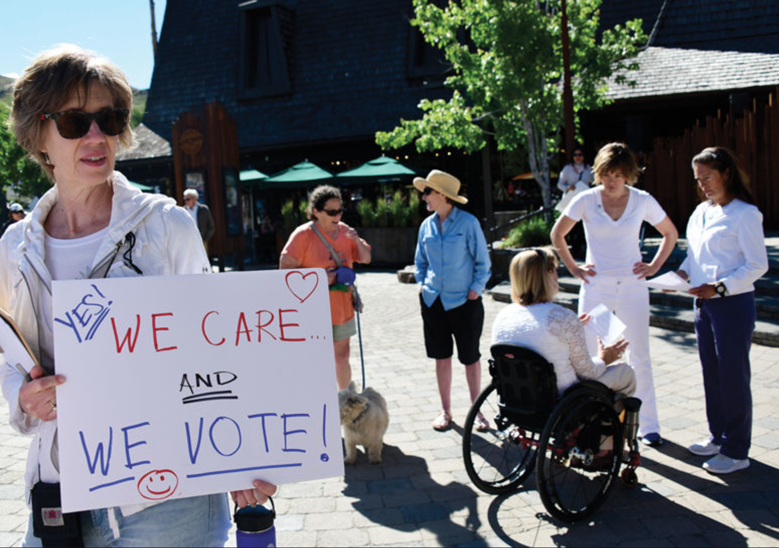 Participants in Saturday's rally held signs and marched through downtown Ketchum. In the background, legislative candidate Muffy Davis speaks to Senate Minority Leader Michelle Stennett, D-Ketchum, right, and rally organizer Bena Larkey, left.  Express photos by Roland Lane