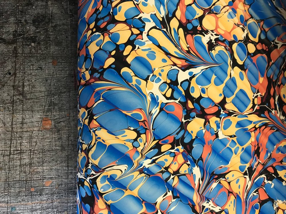 A sample of Jemma's marbled papers in a bright blue and yellow 'Spanish Ripple' pattern.
