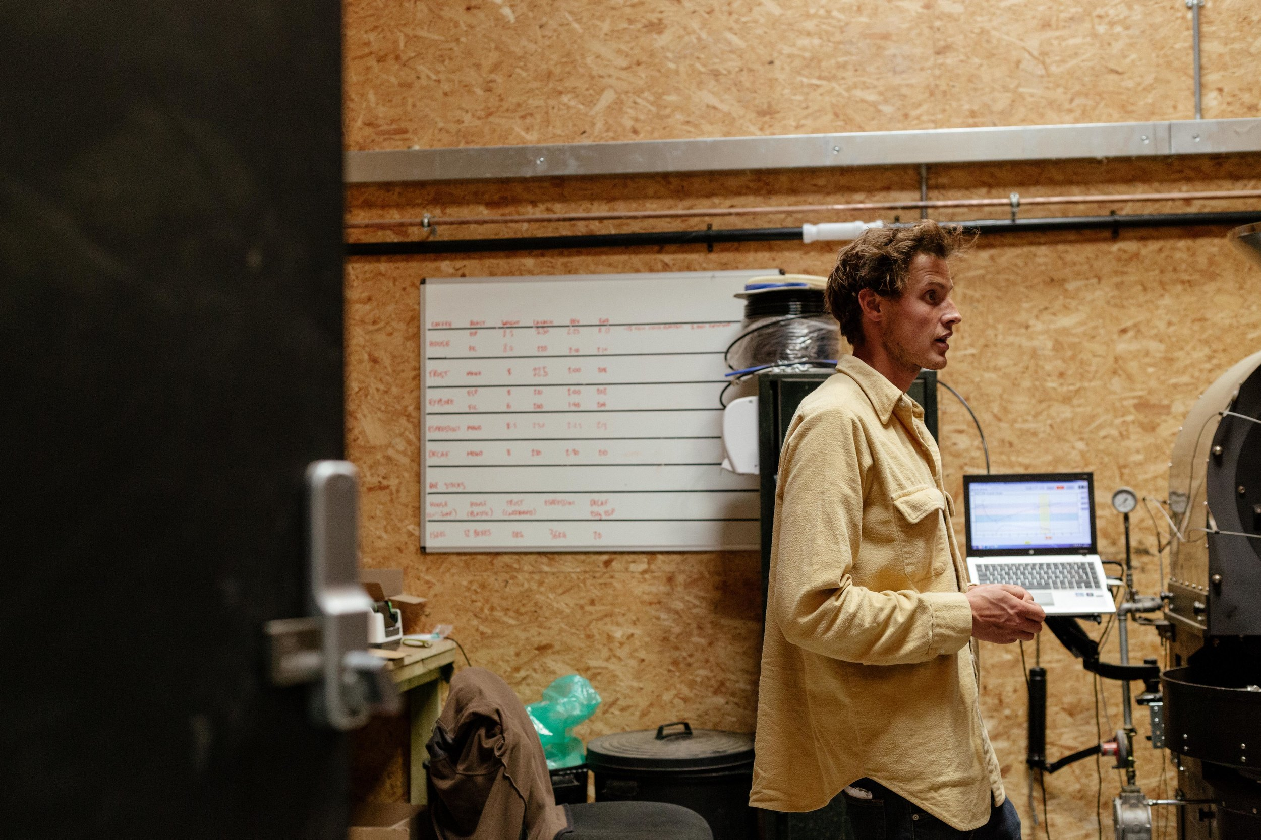 Rich, owner of Yallah Coffee Roasters, stands amongst machines and gadgets in the barn.