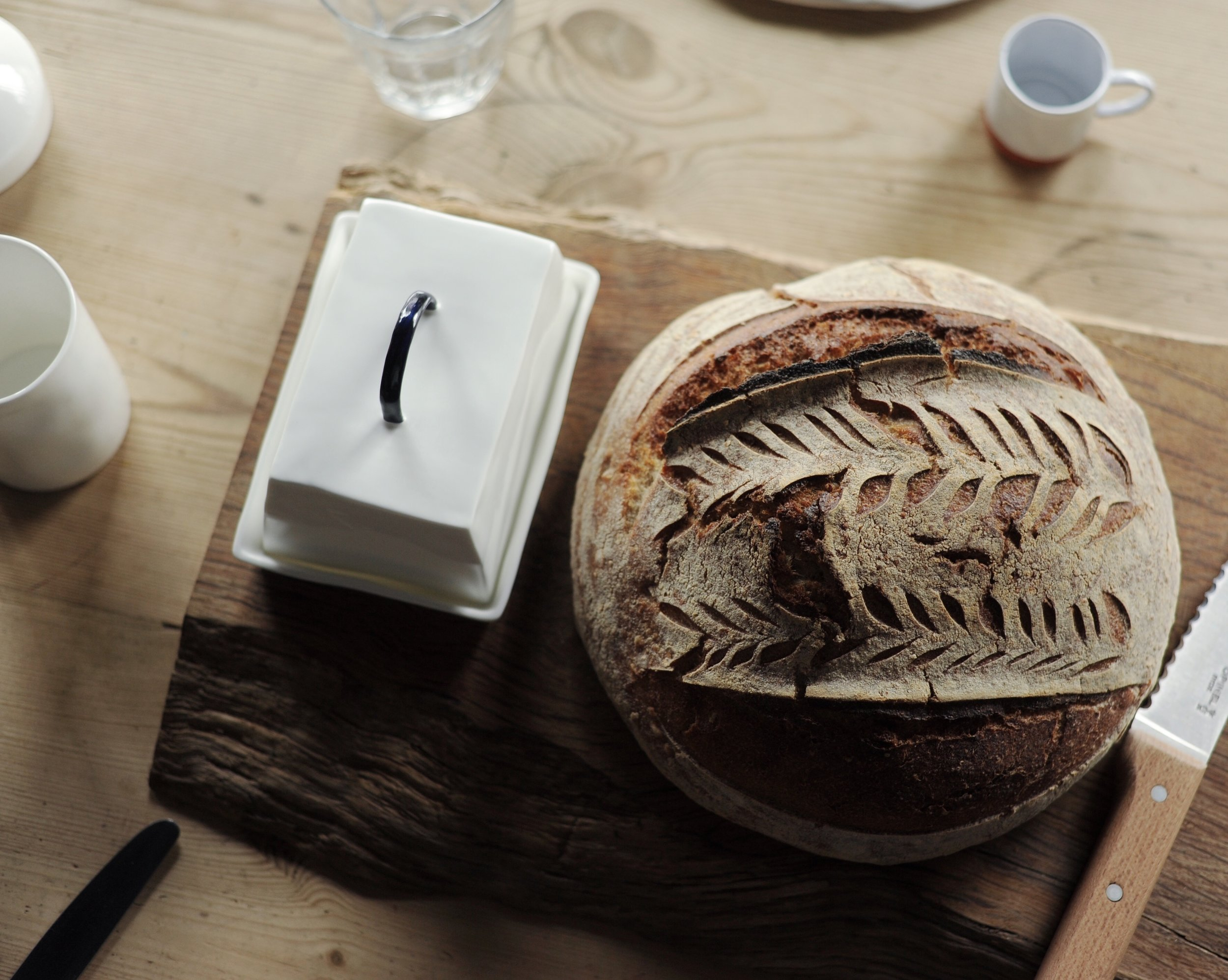 Feldspar homewares, fine bone china butter dish on wooden chopping board, with sourdough loaf.