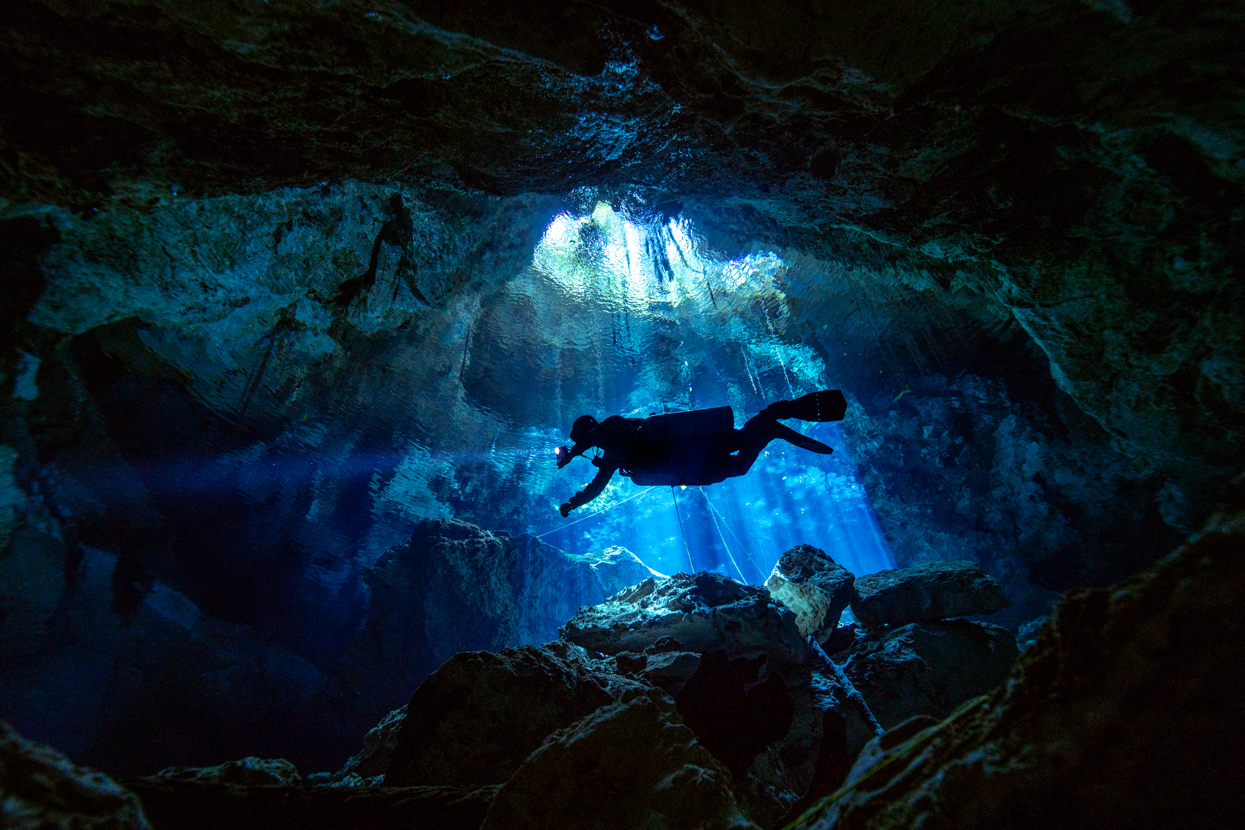 A cave diver enters Systema Taj Ma Ha with light rays depending from a Cenote in the background.