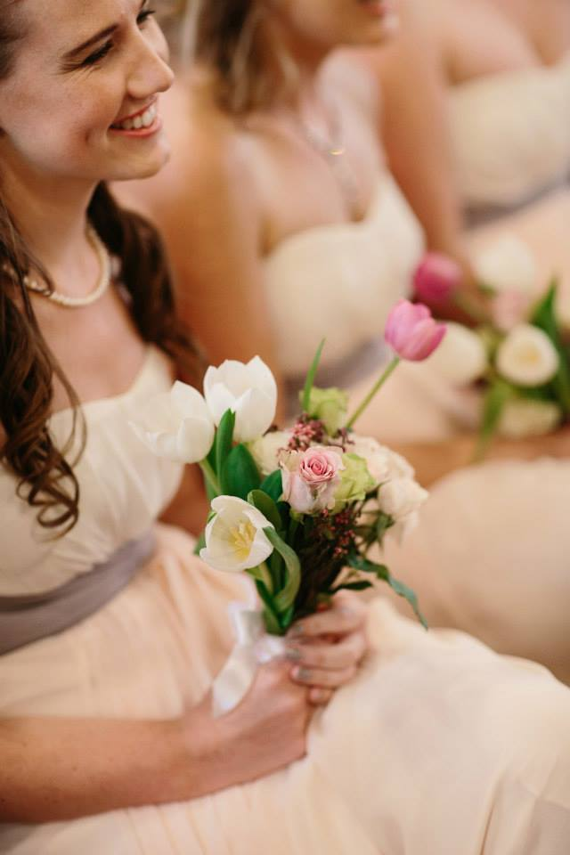 Pastel wearing bridesmaids in the church with tulips and roses
