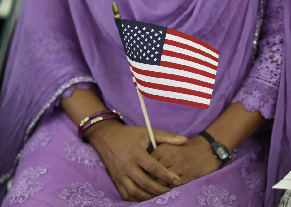 A South Asian woman holds an American flag during a naturalization ceremony in Indianapolis. (Michael Conroy/AP)