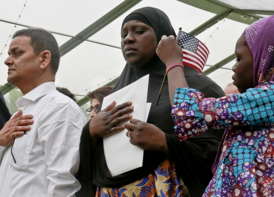 Fatoumata Jangana, center, stands for the National Anthem as her daughter fixes a miniature flag onto her hijab, during U.S. Citizen and Immigration Services ceremony for new citizens. (AP Photo/Bebeto Matthews)