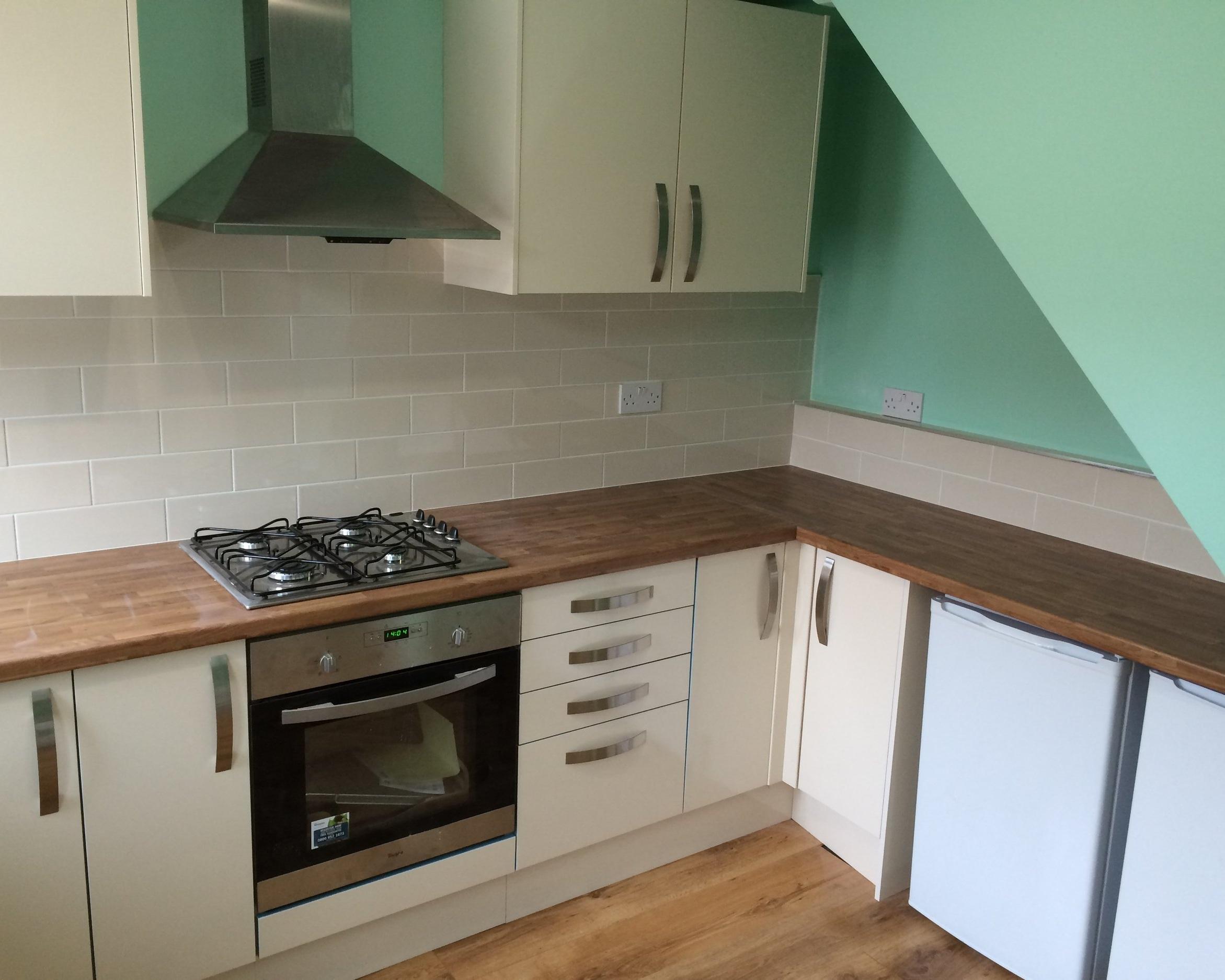 Cream kitchen with brown wooden worktops