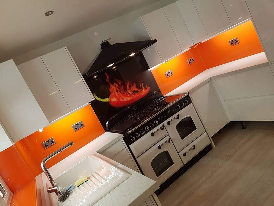 Modern white handle-less kitchen - With colourful glass and feature stove splashback