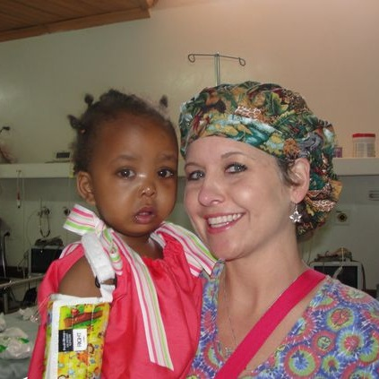 Arkansas children's hospital nurse caring for Kenyan child wearing one our divas dressing darlings dresses. This mission was in partnership with arkansas children's hospital and the nonprofit, change of face.