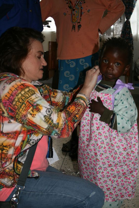 Arkansas children's hospital Doctor, Dr. Lisa Buckmiller, assisting Kenyan child wearing one our divas dressing darlings dresses. This mission was in partnership with arkansas children's hospital and the nonprofit, change of face.