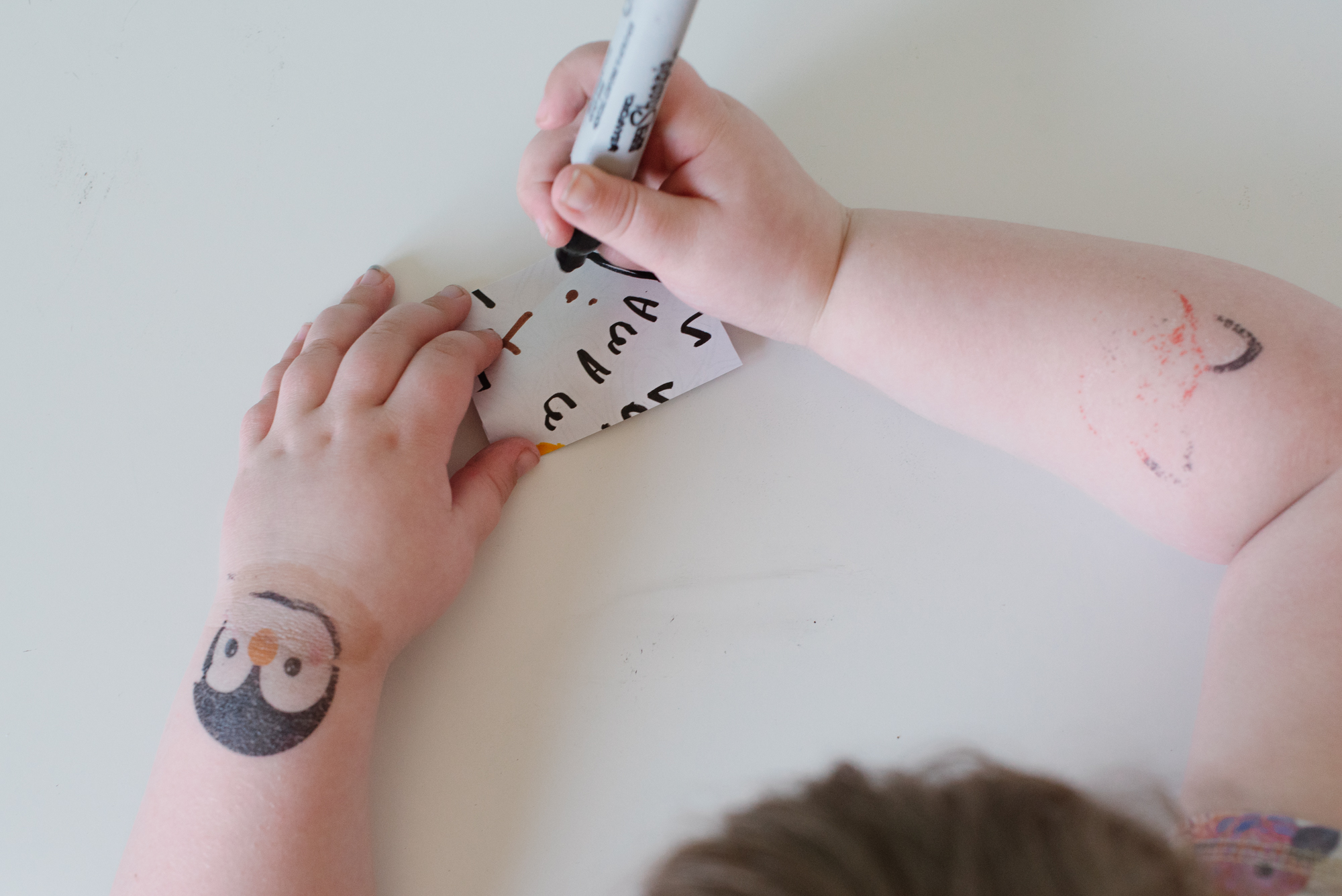 """Little hands writing the word """"mama"""" in a sharpie marker"""