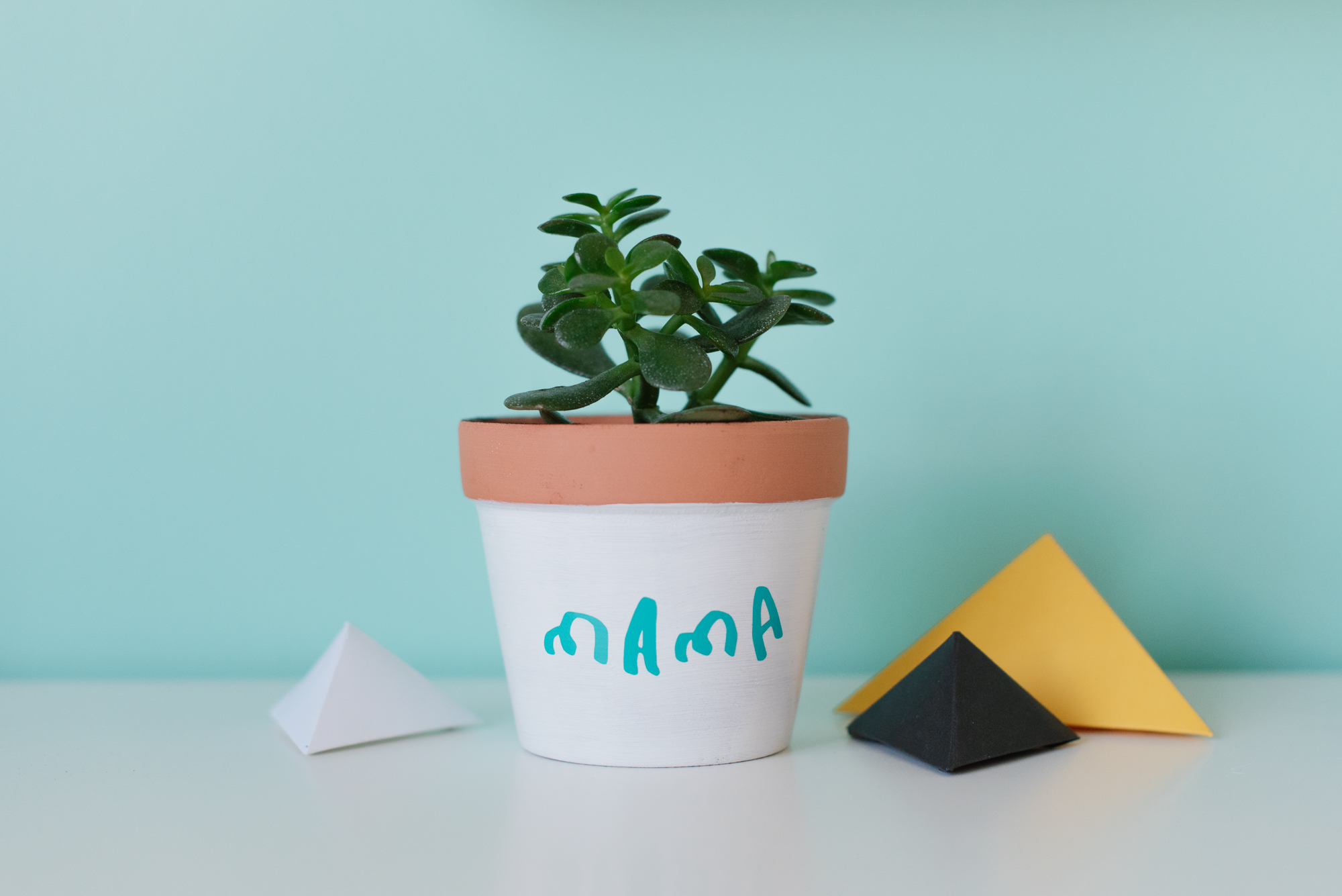 """A painted flower pot with the words """"mama"""" in vinyl lettering"""