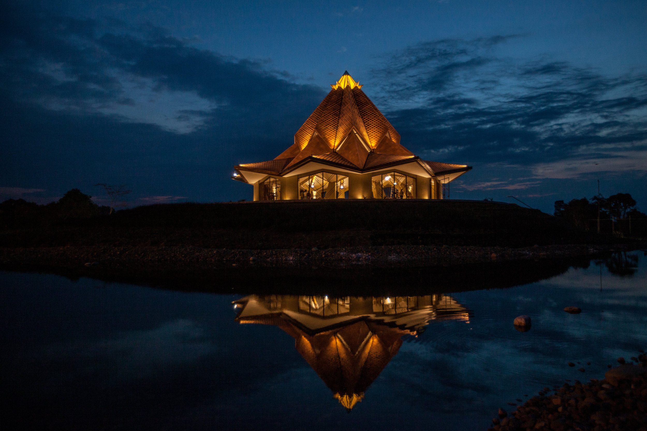 The yellow structure that crowns the Temple, representing the blooming cocoa flower, is made of a fluorescent material that absorbs sunlight in the day and lights up naturally with the sunset.  Source of photos:  Bahá'í World News Service  (copyright © Bahá'í International Community).