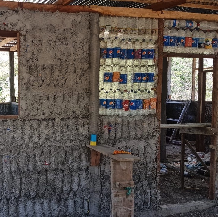 The lower bottles are filled with sand and mud. The upper bottles must be empty so that the walls are stable and the heat can be isolated.