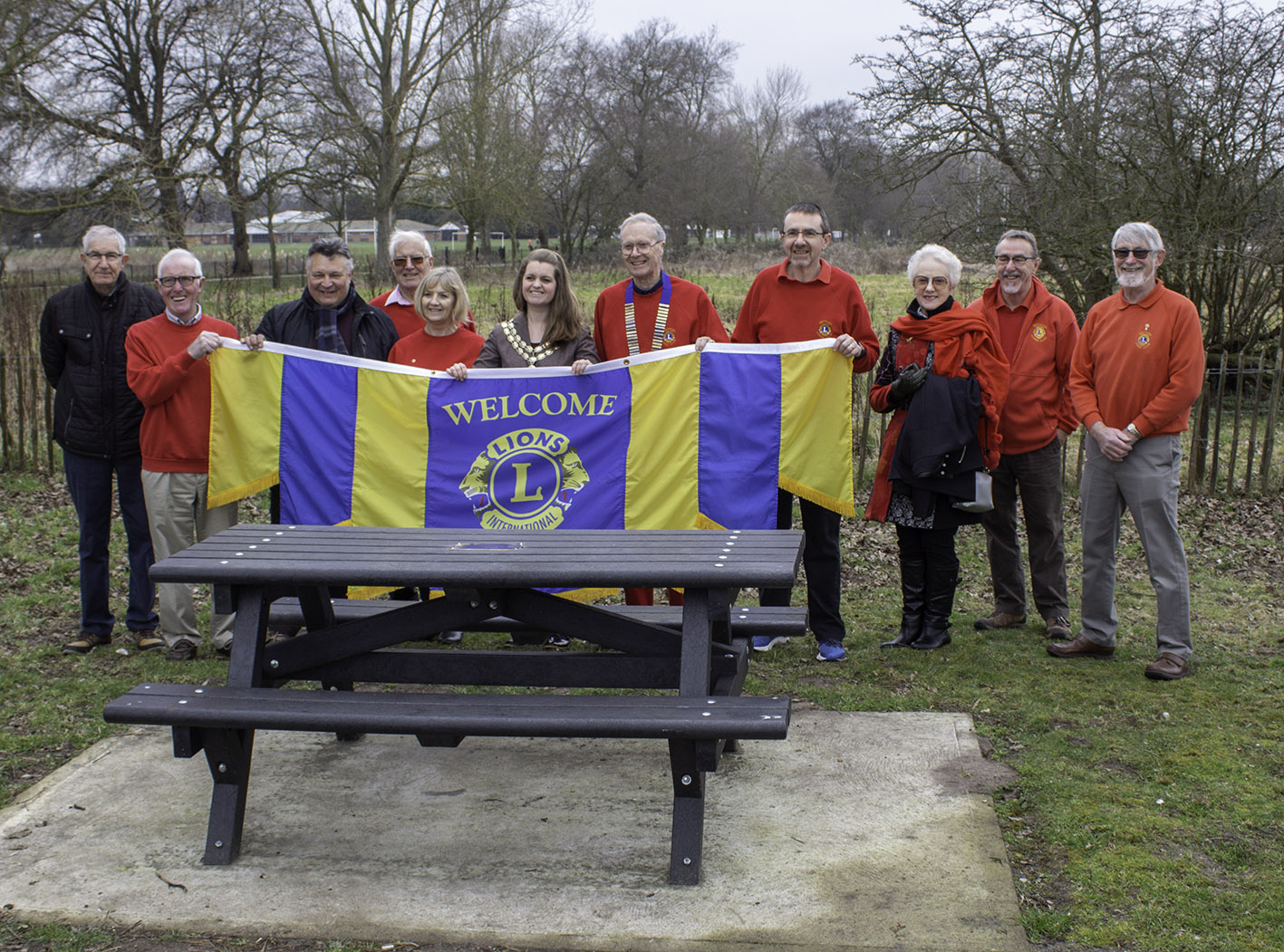 Lion President Chris Lambert and the Mayor of Beccles - Cllr Elfrede Brambley-Crawshaw in the centre surrounded by members of Beccles Lions Club and friends at the Presentation of the Picnic Benches.