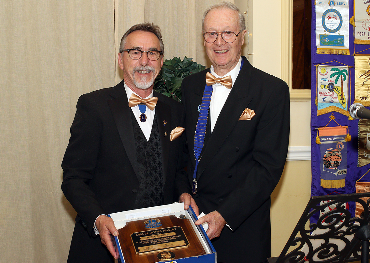 Lion Keith Moore (left) receiving the commemorative 'MJF' plaque from Lion President Chris Lambert.