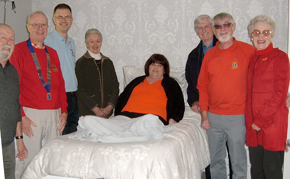 Mrs Sue Foster on the new Bed surrounded by representatives from Beccles & District Lions Club, Beccles Diamond Jubilee in Sickness Fund, Beccles Helping Hands and Beccles Townlands Charity who came together to provide it.