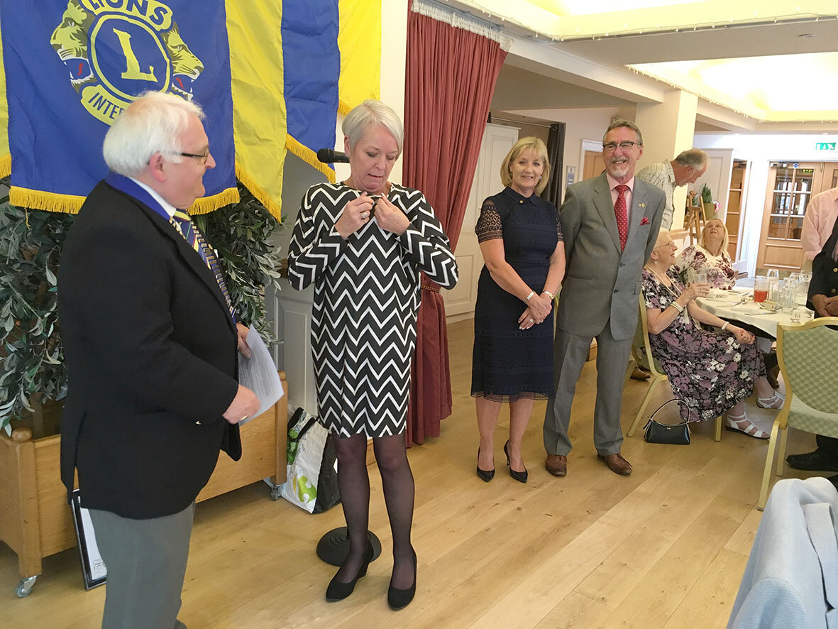 New Lion Dulcie McDonald pinning on her Lions insignia after it's presentation by Lion President Chris Eglington, watched by Dulcie's sponsors for membership - Lions Sharon Page and Keith Moore
