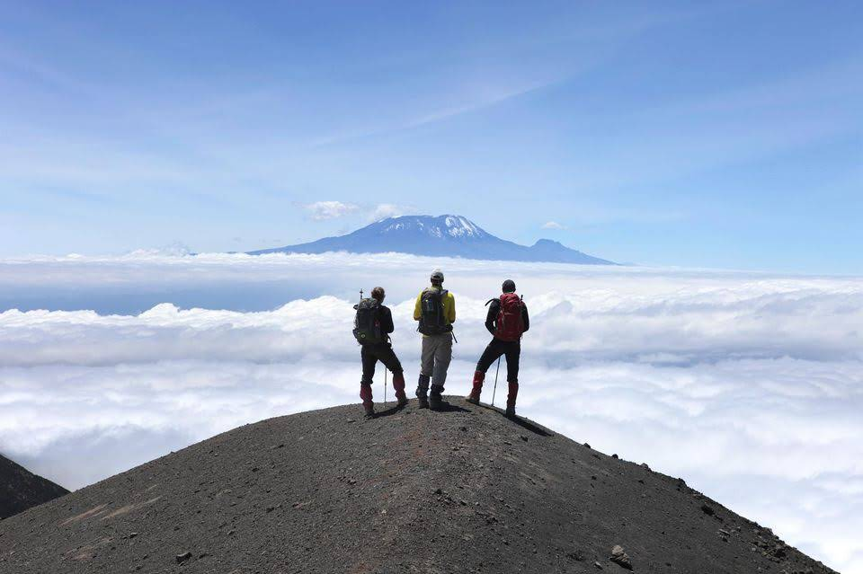 874292-three-hikers-are-looking-at-mount-kilimanjaro-from-the-rocky-ridge-of-mount-meru.jpg