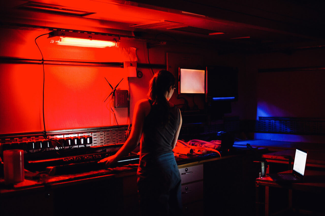 JC123, RRS James Cook, 2015. In the ship's dark room, Dr Louise Callard analyses the next batch of core samples.