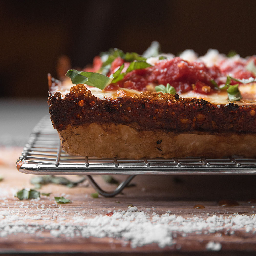 Detroit-style pizza with caramelized dough.