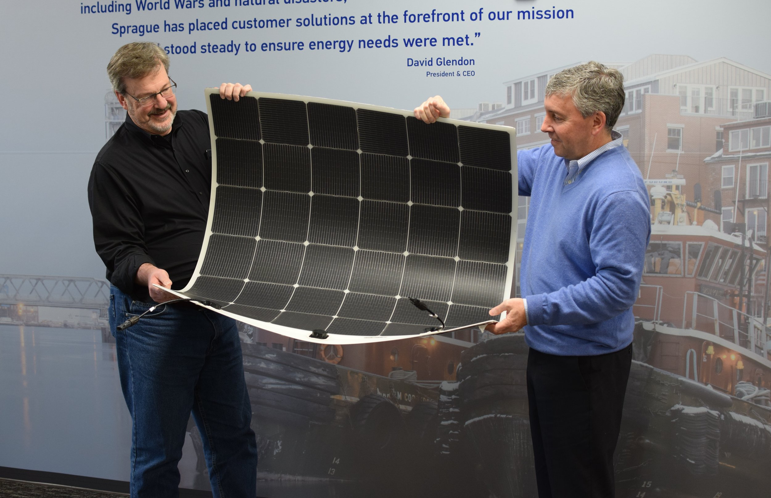 Kevin Maloney, CEO of Picktricity, and David Glendon, CEO and President of Sprague hold one of the solar panels applied to Sprague's South Portland, Maine, terminal tank. The panels are thin, durable, flexible and lightweight, and are closer in size and weight to an all-weather floor mat than to traditional heavy solar panels. Weighing in at under five pounds for a 4'x4' section, the panels can be directly applied to flat surfaces, and are significantly lighter than traditional panels, which also require the additional weight of racks and bolts for installation.