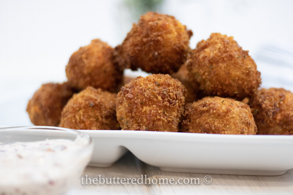 Crispy fried cornbread fritters served with creamy cranberry dipping sauce