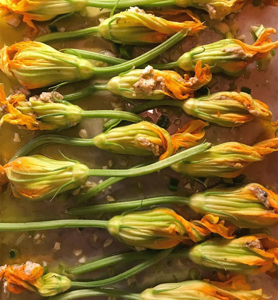 Squash blossoms, the garden's first class envelope for flavor, overstuffed with sheep's milk ricotta, Sicilian pine nuts, eggs, fresh crumb and garden basil, oregano and parsley roasted on a bed of spicy spring garlic.    -  #dinner #gardenfood #keepingvampiresaway  (at At Home in Napa)