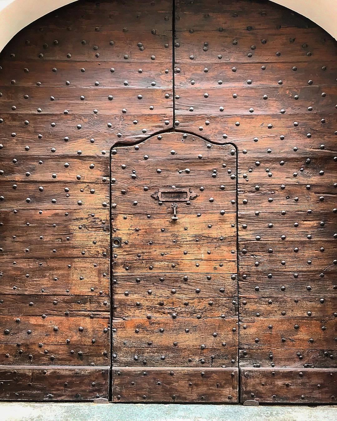 A wicket gate, a door within a door, was important in the Middle Ages.  The larger gate, used to allow horse-drawn carriages  into the interior yard, didn't need to be swung open for pedestrians, thus controlling access and offering greater safety from marauders storming the gates.  -  #italy #piedmont #door #woodworking  (at Bra, Italy)