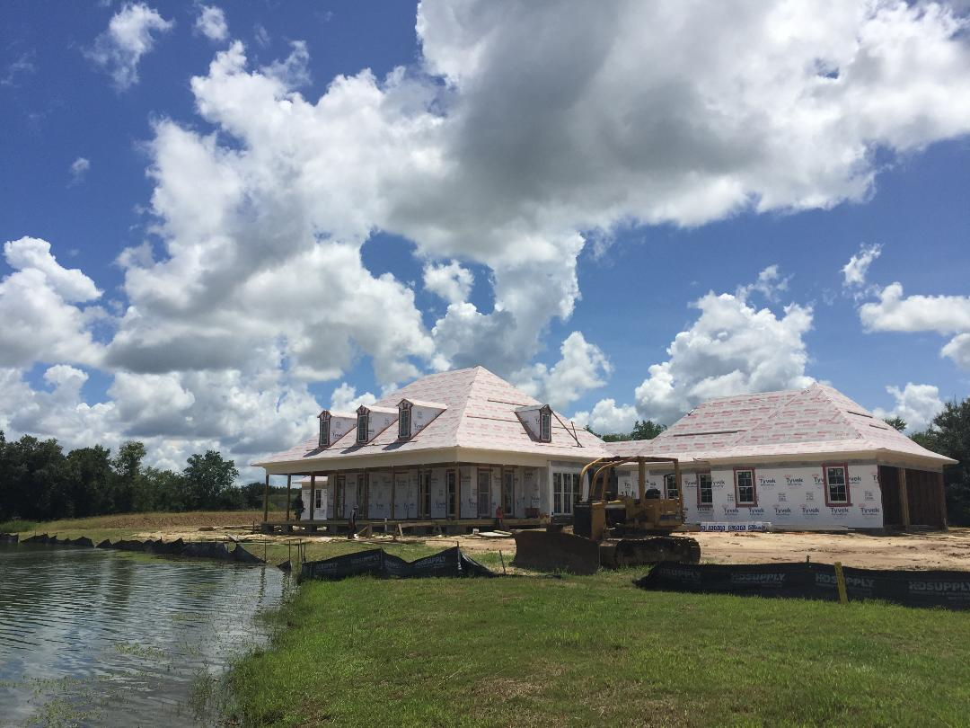 The acadian-style home is situated to follow the curve of the pond.