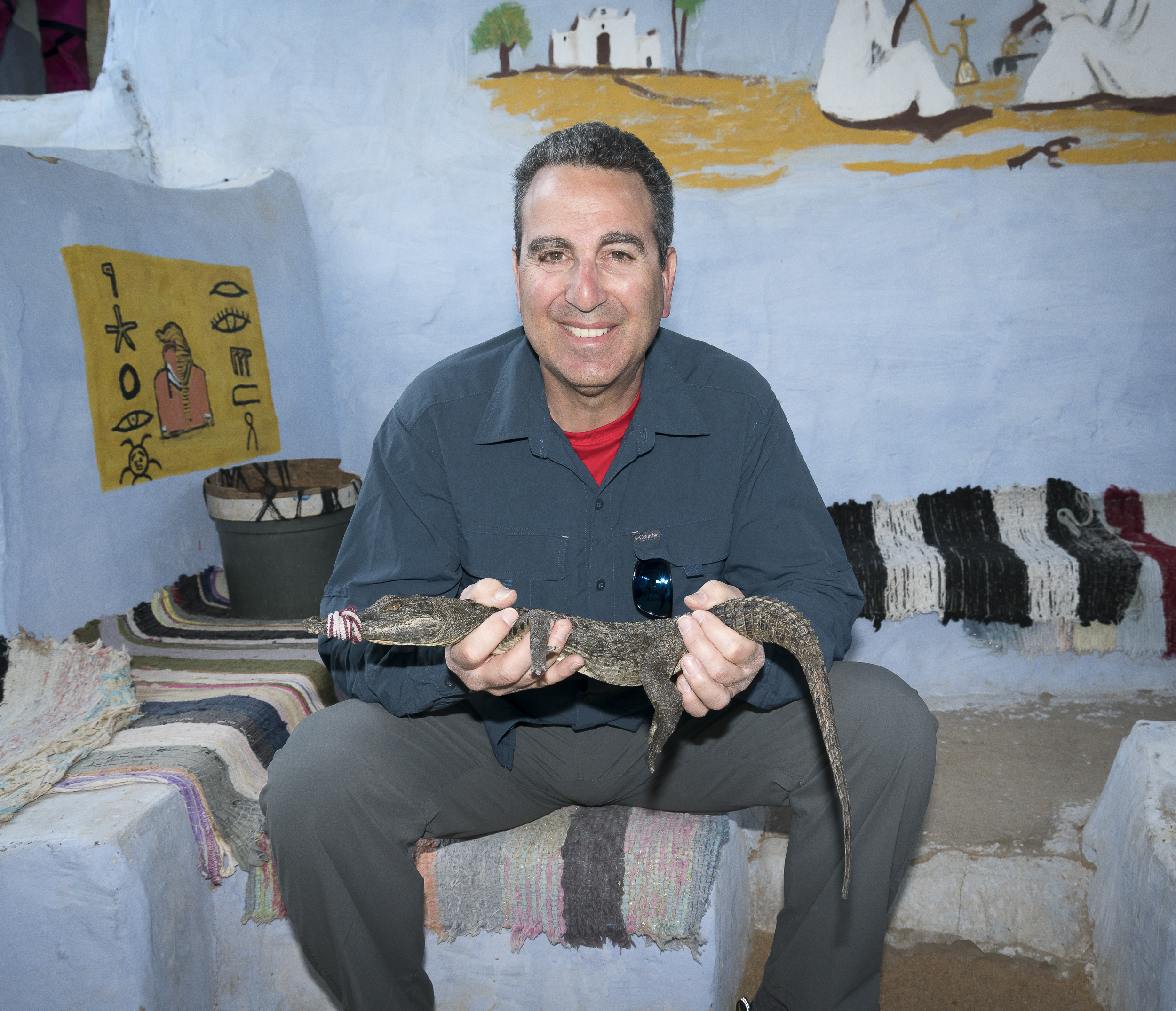 Steve and the crocodile. Note the wall painting above his head that reminds the family of what they once had.