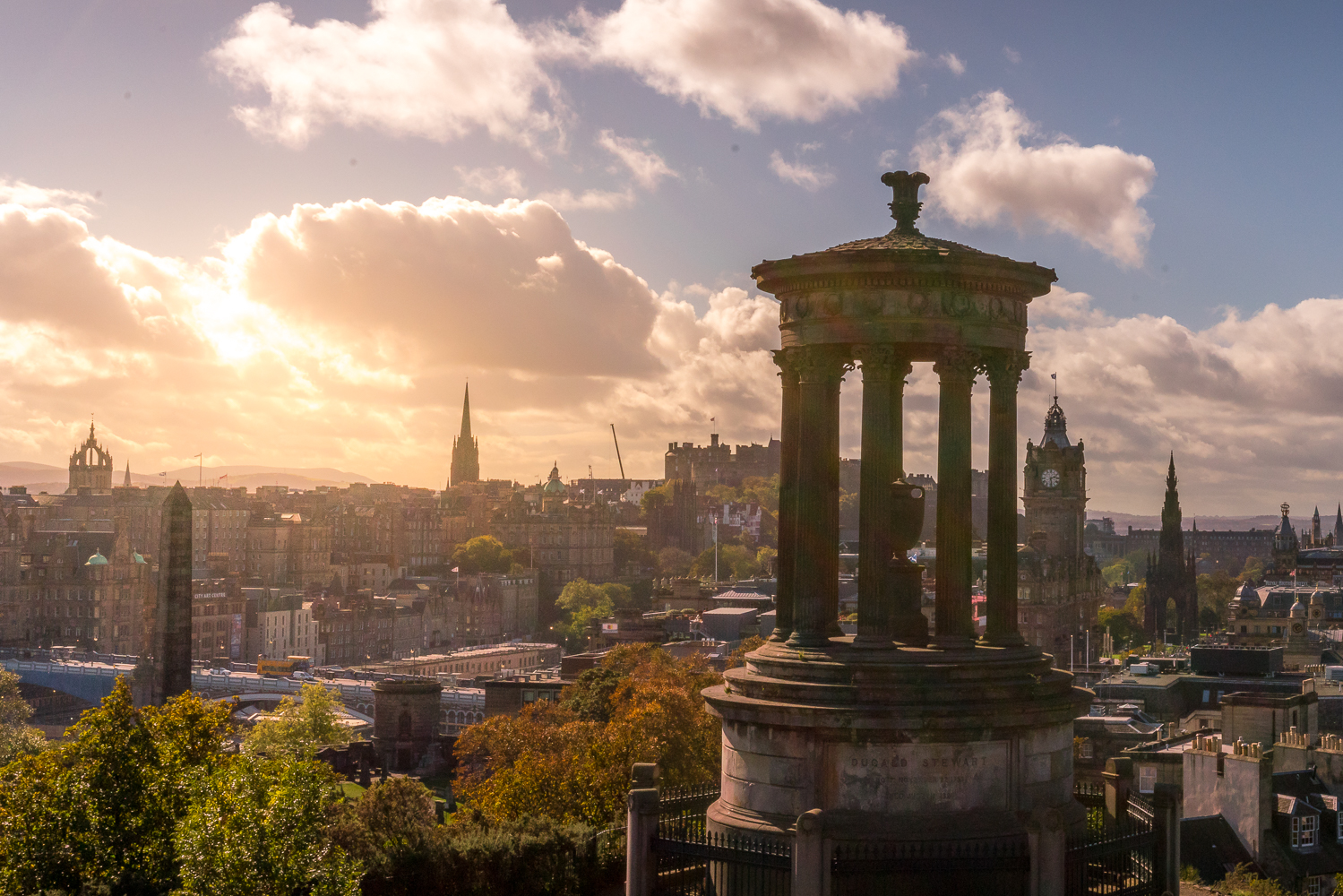 View over Edinburgh in late afternoon sun, with Edinburgh castle in distance.