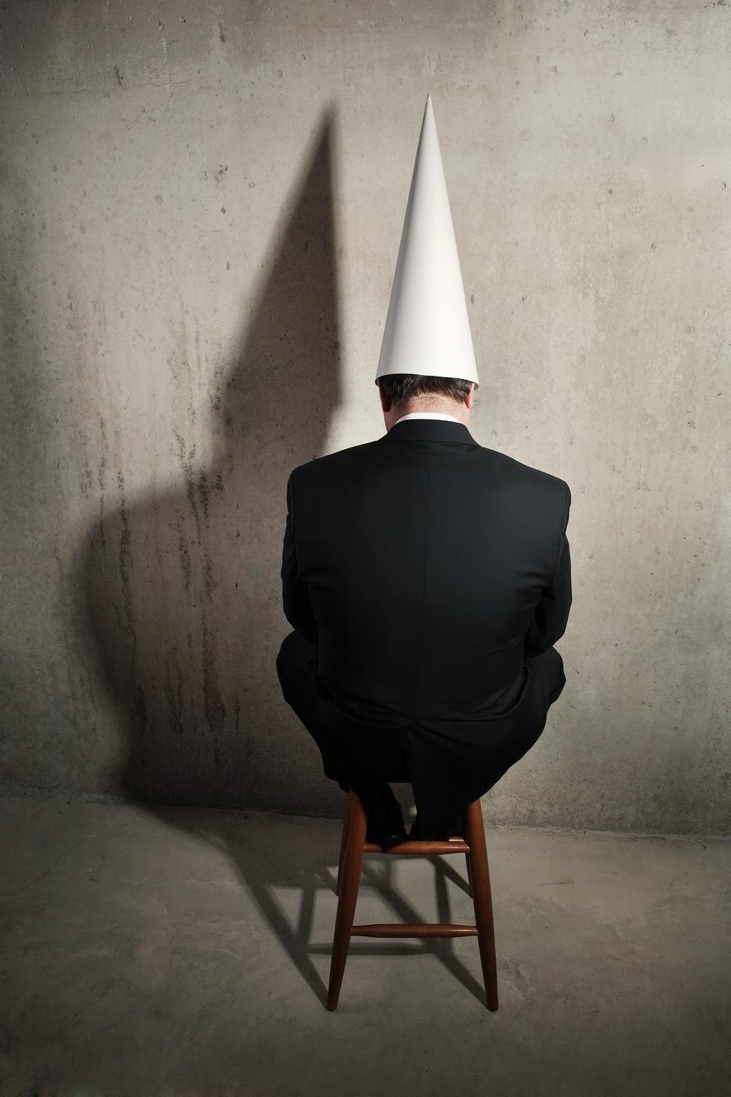 Businessman-wearing-a-dunce-c-16442645.jpg