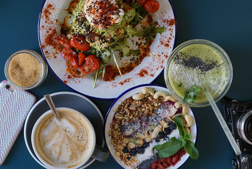 Breakfast on a blue table at Tinman Berlin, including flat white coffee, a green smoothie, Acai bowl with granola, blueberries, almonds, cashew nuts, raspberries, coconut sprinkles and mint and a plate with mashed avocado and poached egg on top.