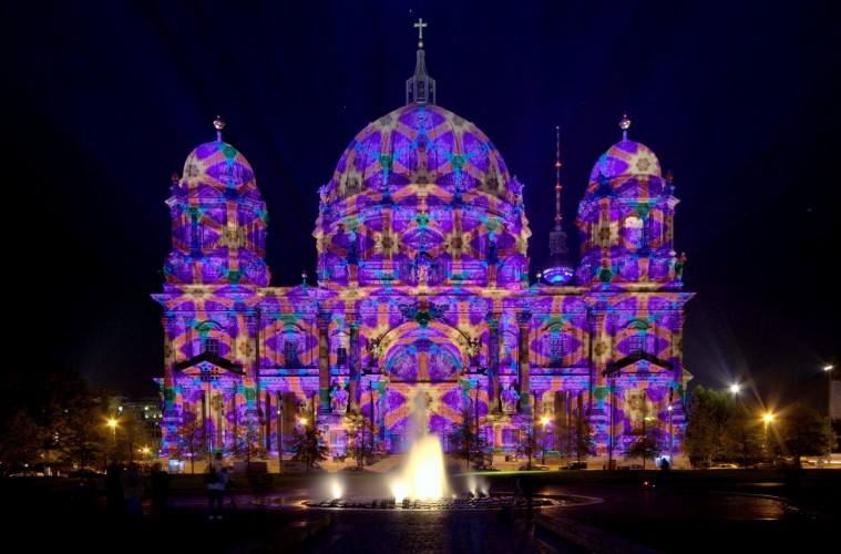 Berlin cathedral church lit up in different colours against the dark sky during festival of lights